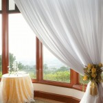 We framed the gorgeous view of the golf course hills with sheer white draping and bouquet tie backs.