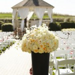 Tall arrangements of roses, orchids and hydrangeas with delicate hanging crystals mark the walk down the aisle