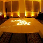 An M & M monogrammed gobo shines on a white dance floor flanked with leather ottomans